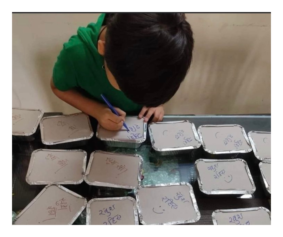 Viral pic: Boy writes good wishes on meal boxes for COVID-19 patients; wins hearts